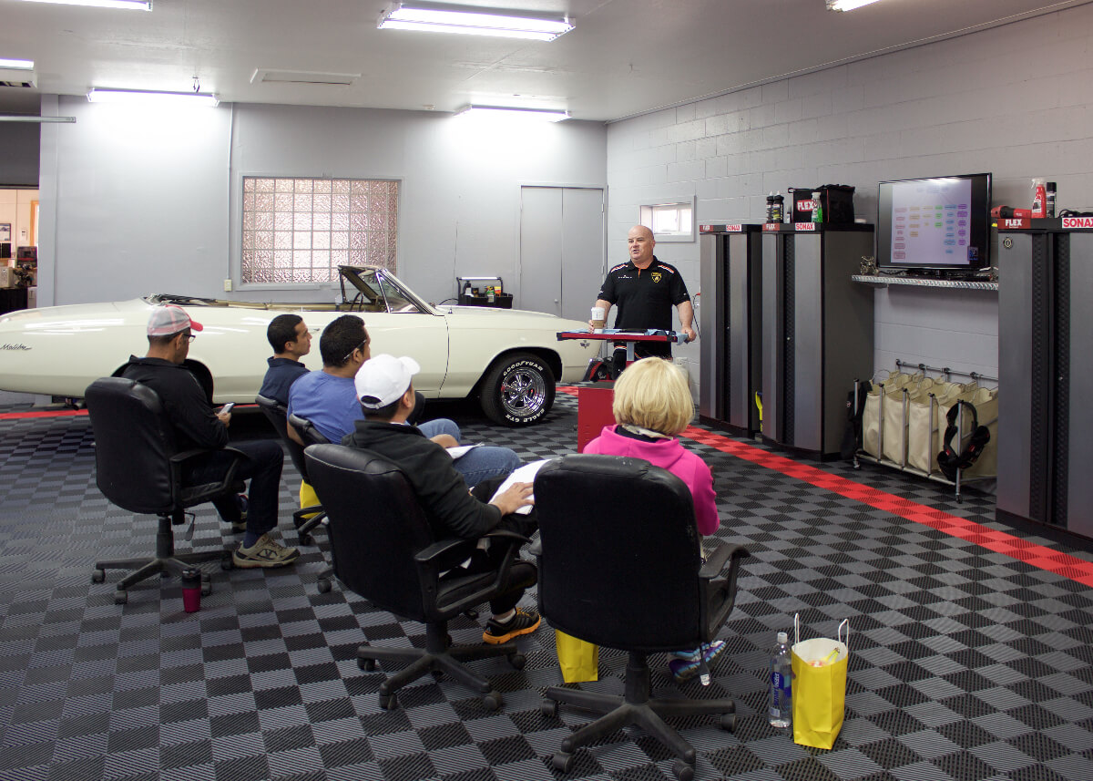A detailing center with Free-Flow, a Chevy Malibu, and crew
