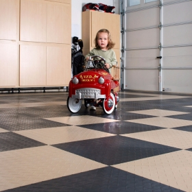 Girl with a toy fire truck in a home garage with RaceDeck XL flooring.