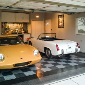 A garage with CircleTrac flooring, a vintage Lotus and and a vintage MG Midget