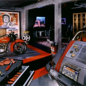 A man cave with a vintage indian motorcycle, a classic Porsche, and RaceDeck Garage Flooring.