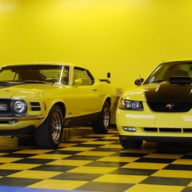 New and classic Mustangs in a brightly colored garage