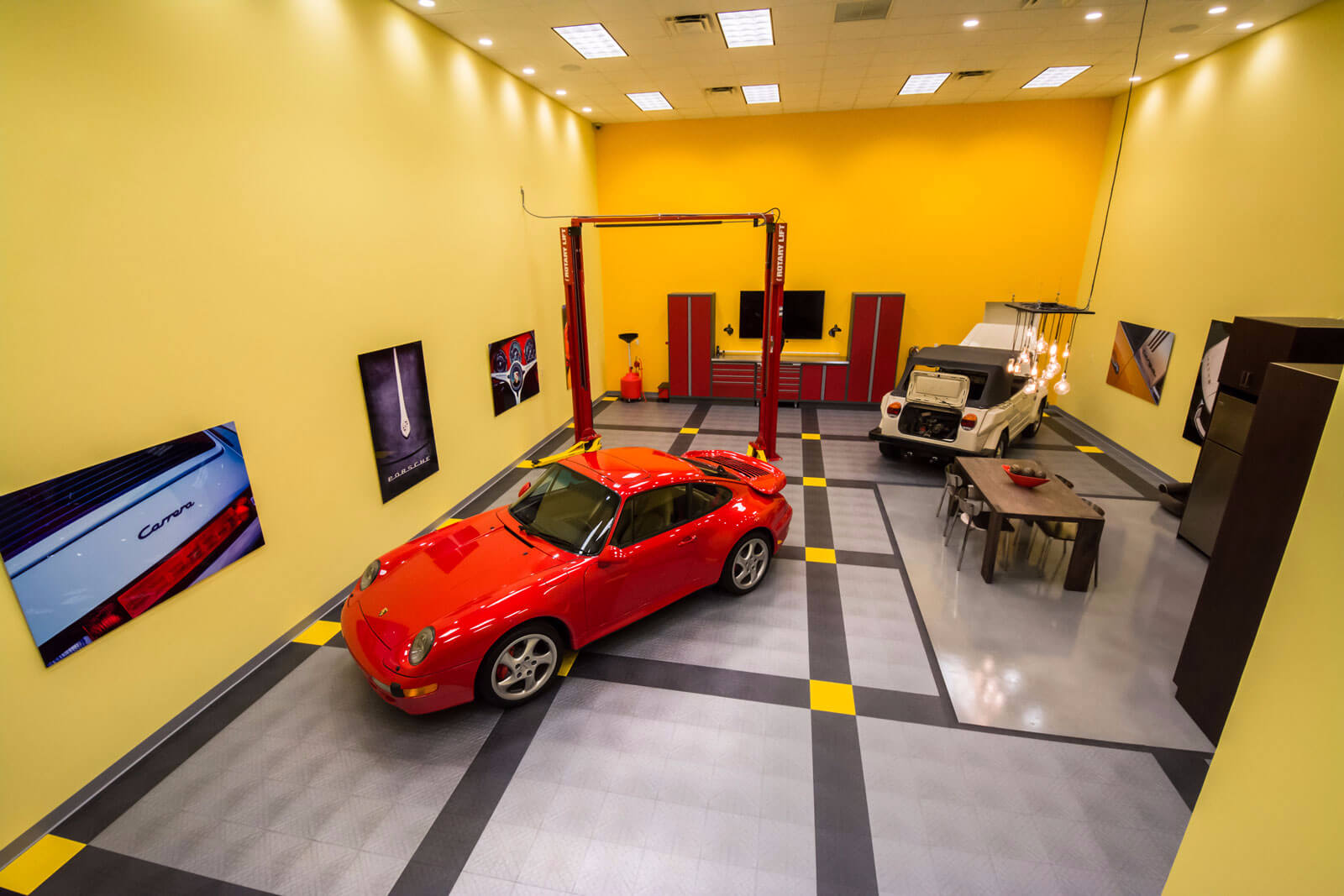 A Porsche and a VW thing in a garage with a lift and CircleTrac garage flooring