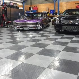 A shop with two Cadillacs and RaceDeck XL garage flooring