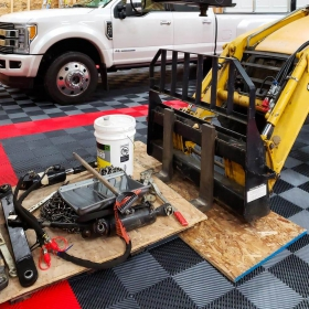 A front end loader with forks and a Ford F450 parked on  Free-Flow XLC commercial-grade garage tiles