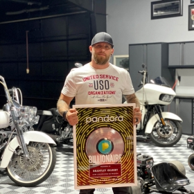 Brantley Gilbert shows his Pandora Billionaire award among his motorcycle collection in his RaceDeck Free-Flow garage
