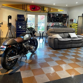 A garage with a BMW motorcycle, a bike, shop equipment, a couch, and RaceDeck garage flooring tiles.