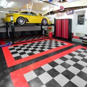 Yellow Porsche and lift in a 3-car garage with RaceDeck Diamond flooring.
