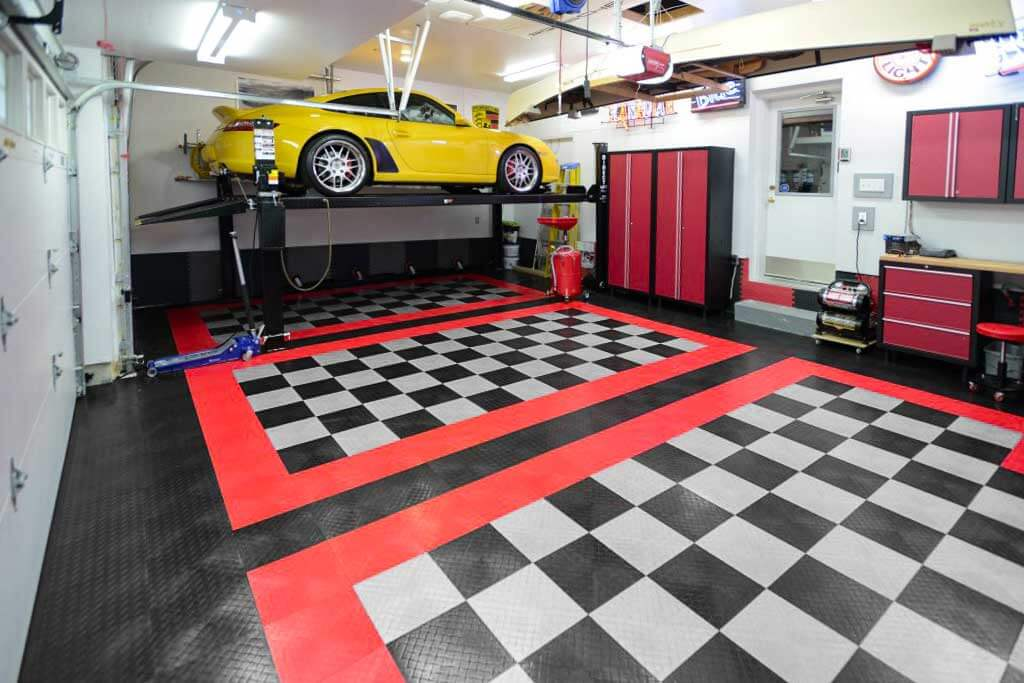 Yellow Porsche on a lift in this 3-car garage with RaceDeck Diamond flooring.