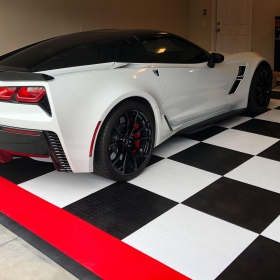 Corvette in a black, white, and red RaceDeck Diamond garage with edging.