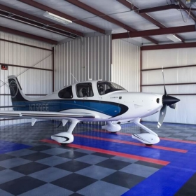 Airplane hangar floored with RaceDeck Diamond Graphite, Alloy, Royal Blue, and Red