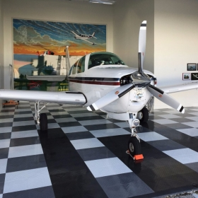 An airplane in a hangar with RaceDeck Diamond flooring and TuffShield.