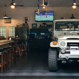 A classic land cruiser and a  cool bar in a garage with RaceDeck garage flooring tiles