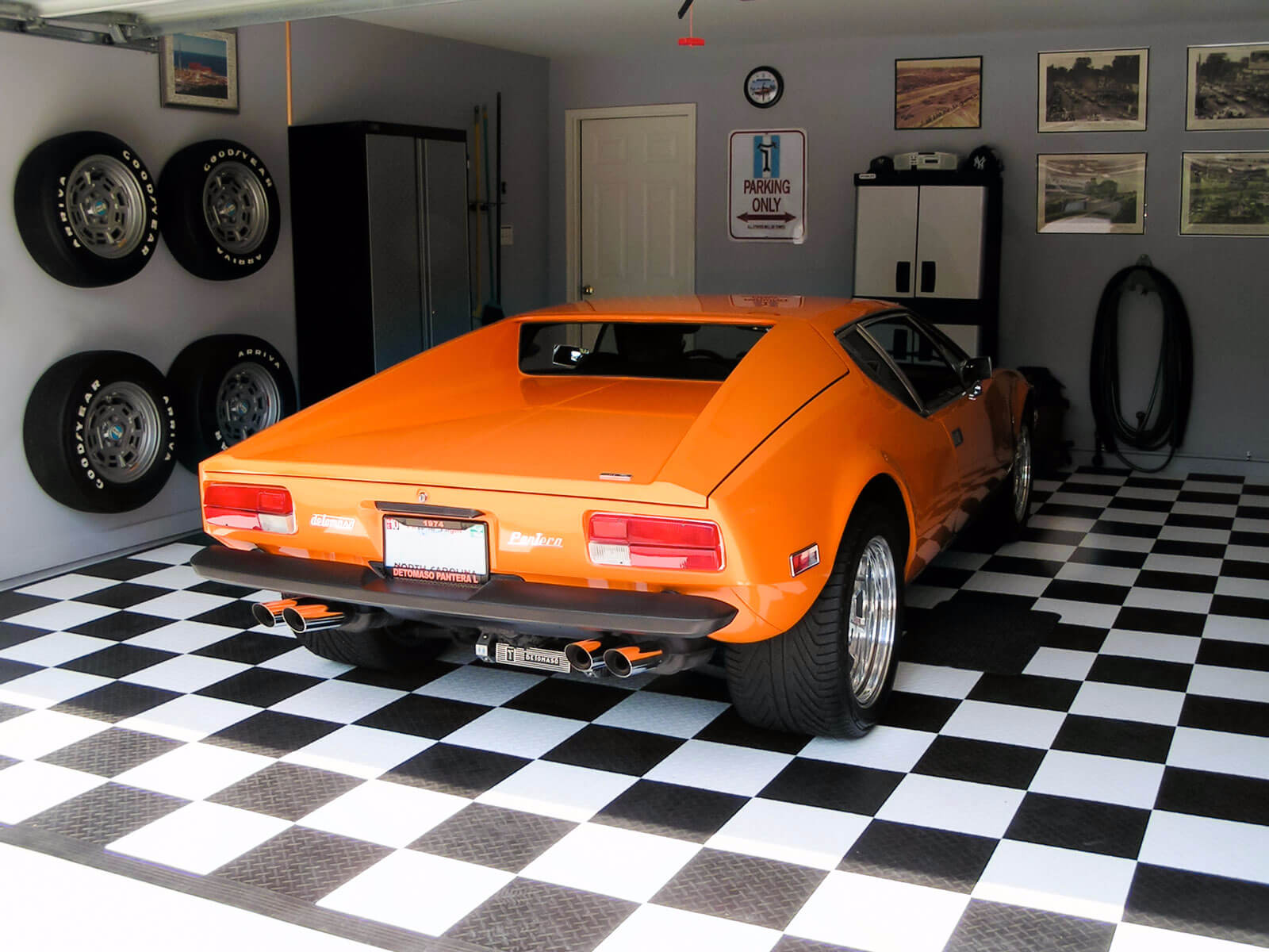 Residential garage with a De Tomaso Pantera and RaceDeck Diamond black and white floor
