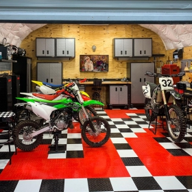 A custom garage floor with the number 32 in red and four dirt bikes.