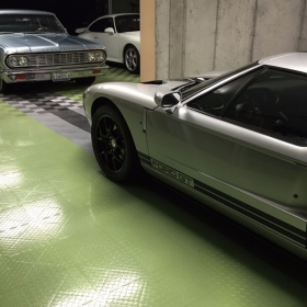 A RaceDeck garage floor with a Ford GT, Chevy Malibu, and a Porsche