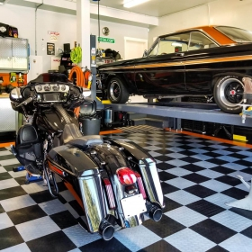 A checkerboard garage floor with a Harley-Davidson touring motorcycle and a Ford Falcon.