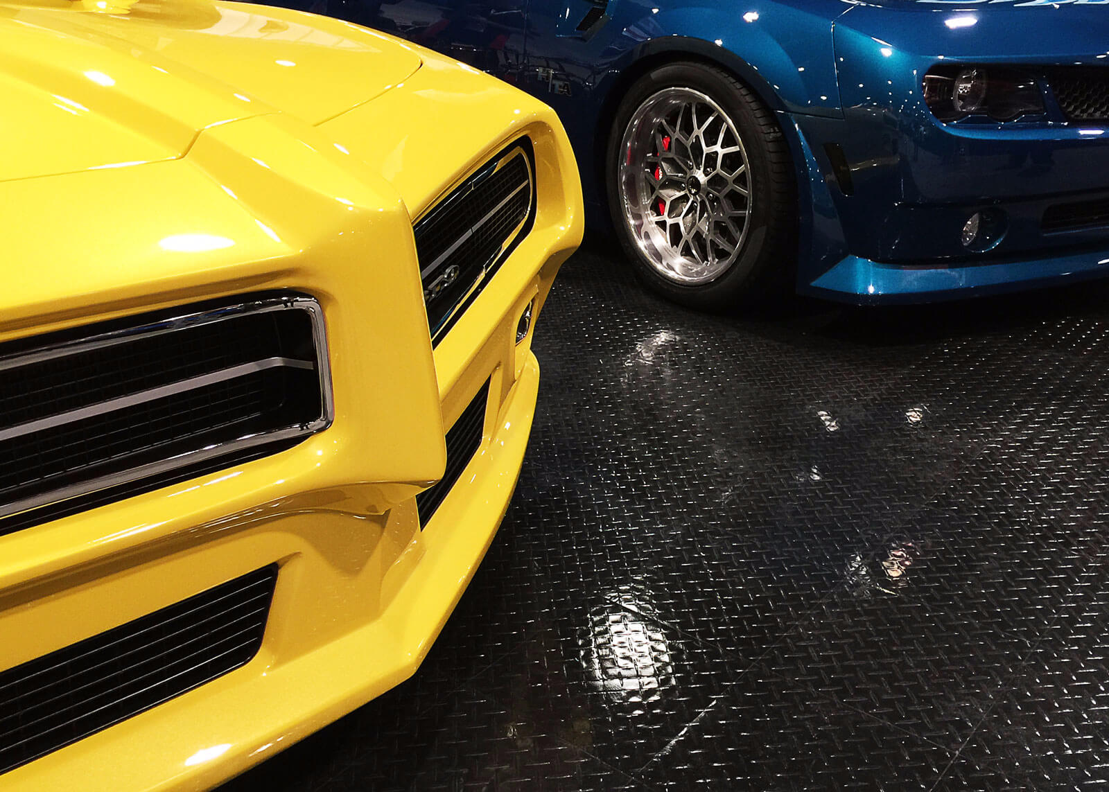 Muscle cars at SEMA on black RaceDeck Diamond with TuffShield