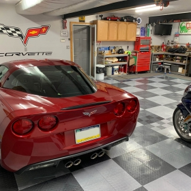 Graphite and alloy RaceDeck Diamond garage with Corvette and motorcycles. Free-Flow allows water to escape to the drain below.