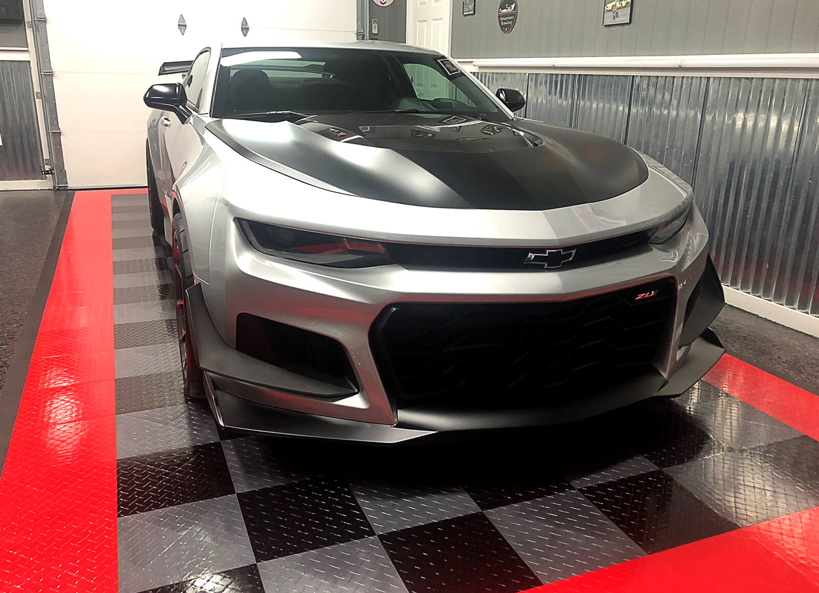 Chevy Camaro ZL1 on a TuffShield Diamond alloy, black, and red parking pad with edging.