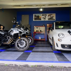 Two BMW motorcycles and a Fiat on a RaceDeck garage floor