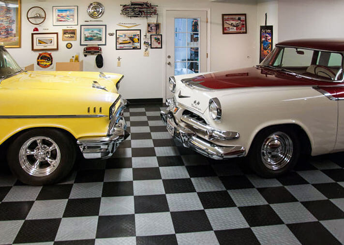Two classic Cadillacs on a black and alloy RaceDeck Diamond garage floor