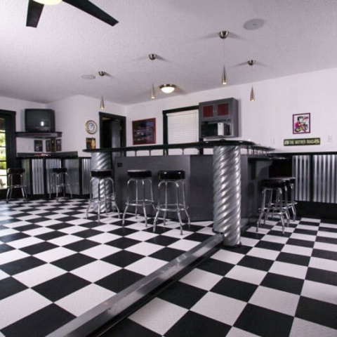 Game room and bar area with RaceDeck Diamond black and white checkered flooring.