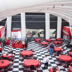 Kelley under tent with red tables