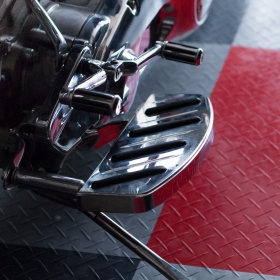 Close-up shot of a motorcycle parked on RaceDeck Diamond flooring.