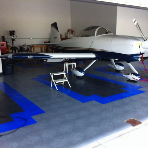 RaceDeck Diamond flooring in a custom pattern with edging for this airplane hangar.