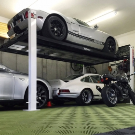Ford GT, Porsche, BMW, and Ducati with in a Free-Flow garage with lift