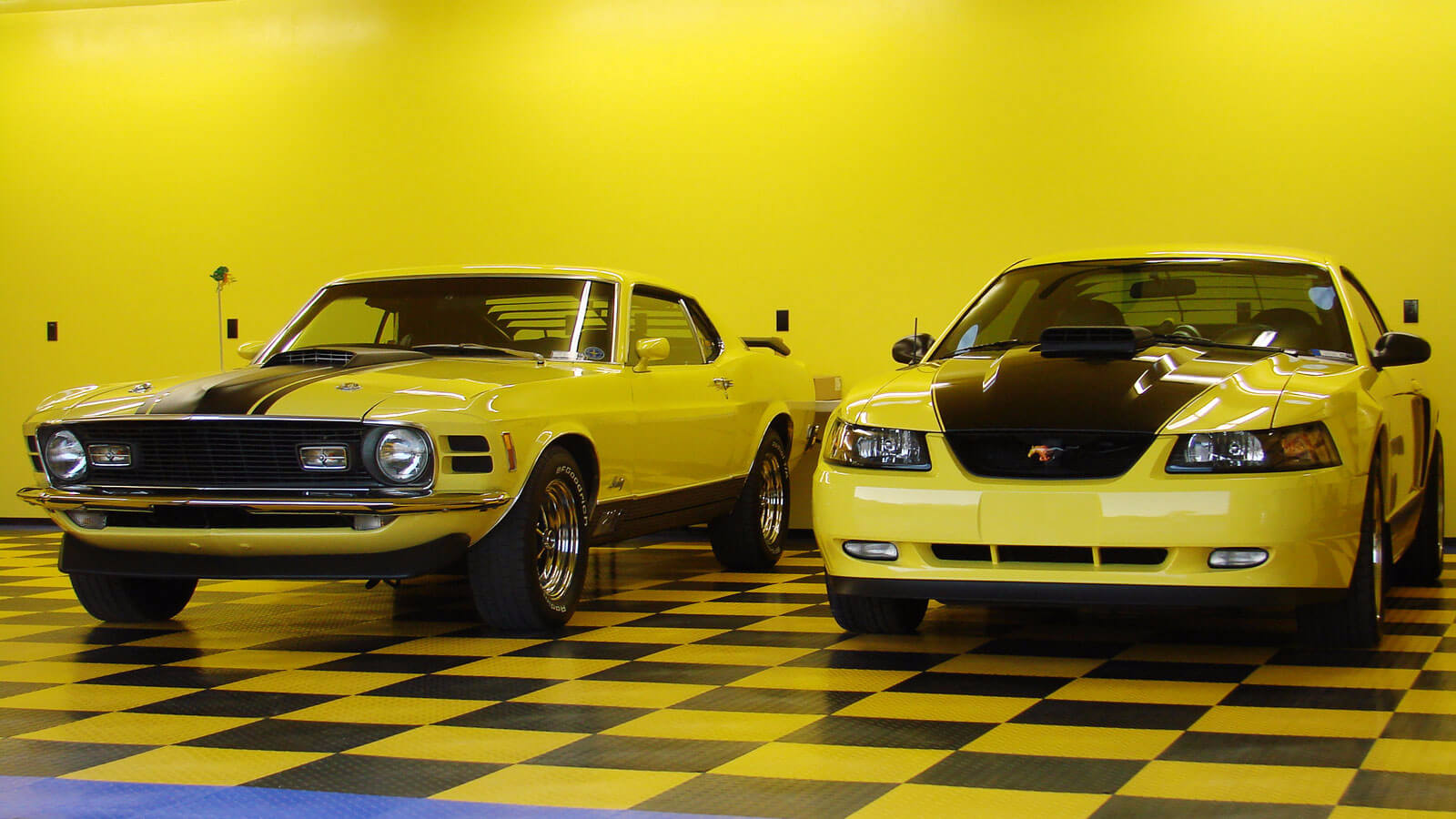 Yellow garage with new and old Mustangs