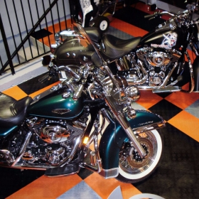 Two Harleys stand on RaceDeck's officially licensed Harley-Davidson® flooring.
