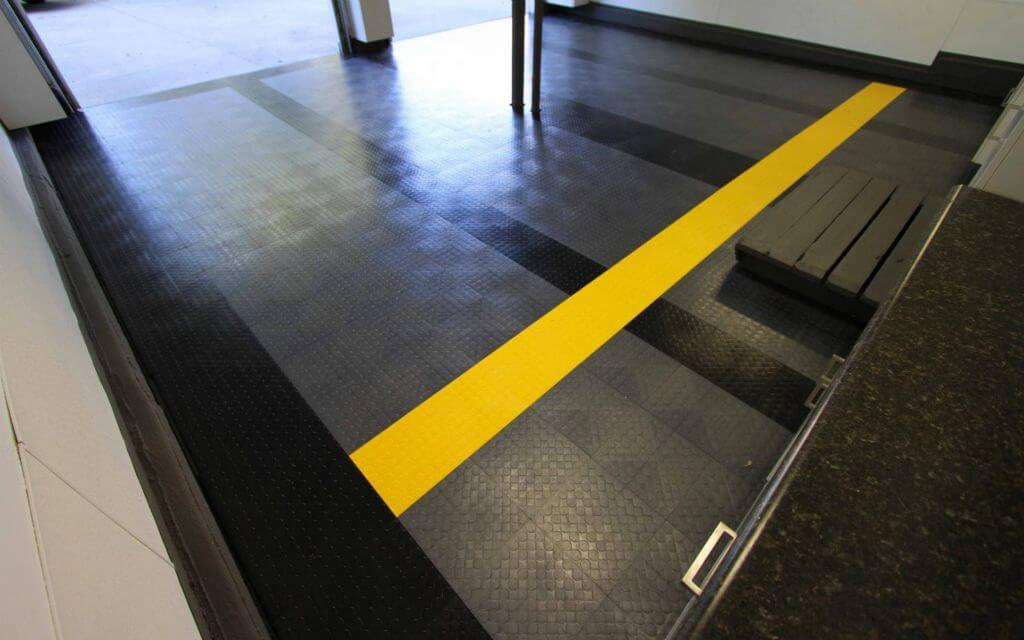 Garage floor with CircleTrac flooring in black, graphite, and a pop of yellow