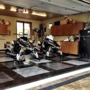 Two snowmobiles in a garage, featuring RaceDeck Diamond black, graphite and alloy, with black edging.