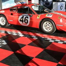 A variety of RaceDeck flooring is used in this red and black race car display.