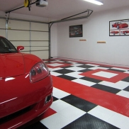 Red Corvette themed garage with RaceDeck Diamond flooring in black, white, and red.
