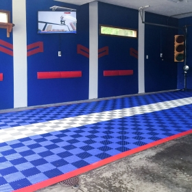 Self-draining Free-Flow royal blue and alloy garage flooring with red edging being used over a drain.