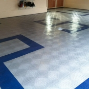 Home garage with custom initial design. RaceDeck Diamond alloy and royal blue with Free-Flow accents over drains