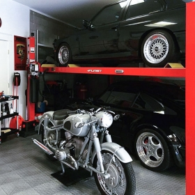 RaceDeck Diamond Alloy garage floors with two-car lift and motorcycle.