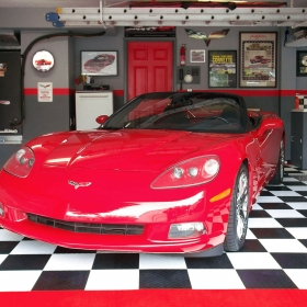 Corvette garage floor with black and white checkered RaceDeck Diamond, red RaceDeck Diamond edges and AccuPark® parking guides