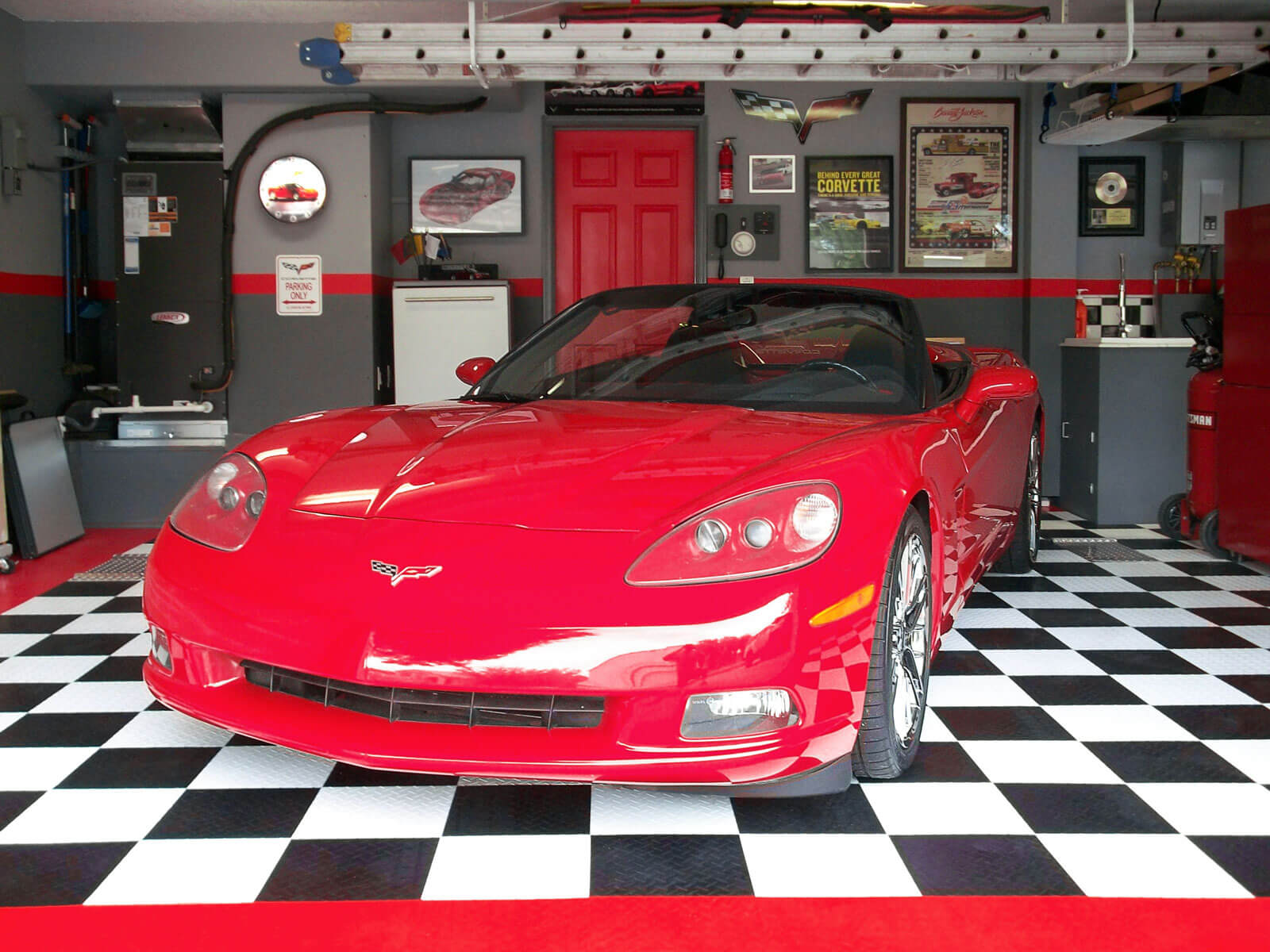 Red Corvette in a garage with RaceDeck Diamond flooring and Accupark parking guides.
