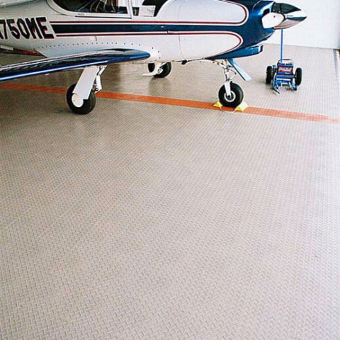 Beige RaceDeck Diamond with orange accent in this airplane hangar.
