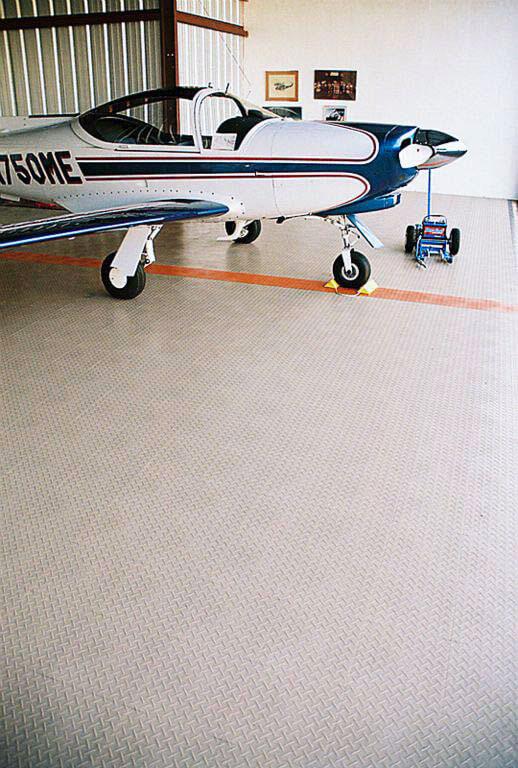 Beige RaceDeck Diamond with orange accent in this airplane hangar.