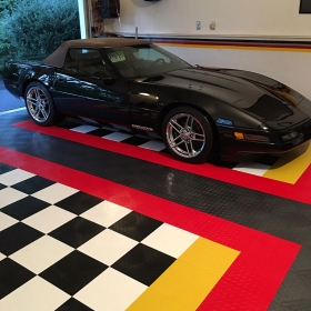 Custom two-car garage with RaceDeck Diamond black, white, yellow and red designs.