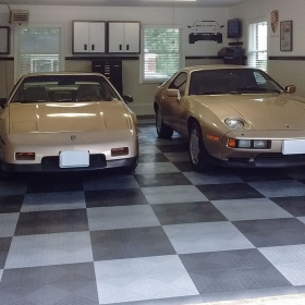 Two cars in a garage with RaceDeck Diamond alloy and graphite flooring.