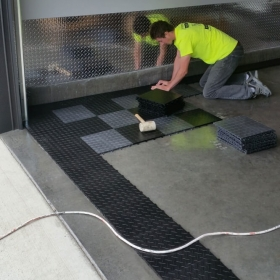Installing a garage floor with a checkered RaceDeck Diamond alloy and black design.