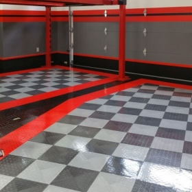 Custom garage floored with RaceDeck Diamond Tuffshield in alloy, red, graphite and black.