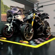 Motorcycle pad display with Free-Flow flooring and yellow edging.
