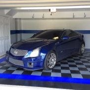A garage with blue accents showcases this blue Cadillac. Flooring: RaceDeck Diamond alloy, black, and royal blue.