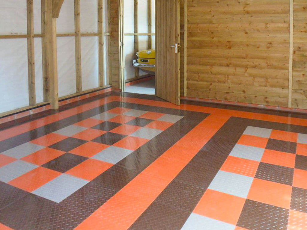 Garage flooring with RaceDeck Diamond in orange, espresso, and alloy colors.
